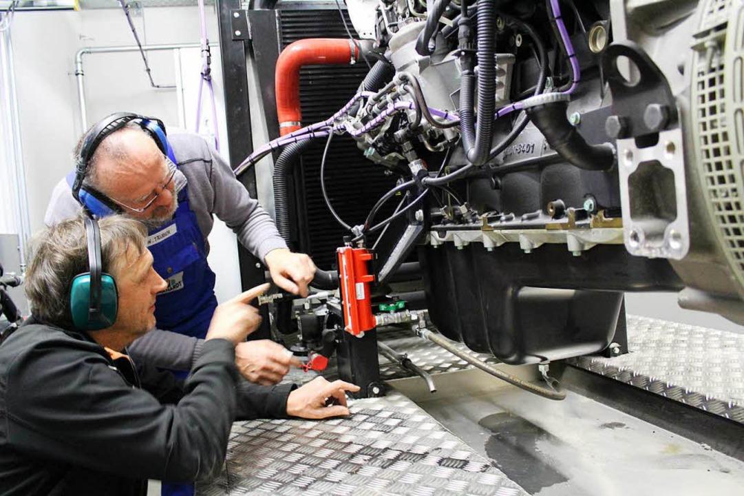 Josef Saier (vorne) und Willi Täuber vor dem mächtigen Lkw-Motor im BHKW  | Foto: Erich Krieger
