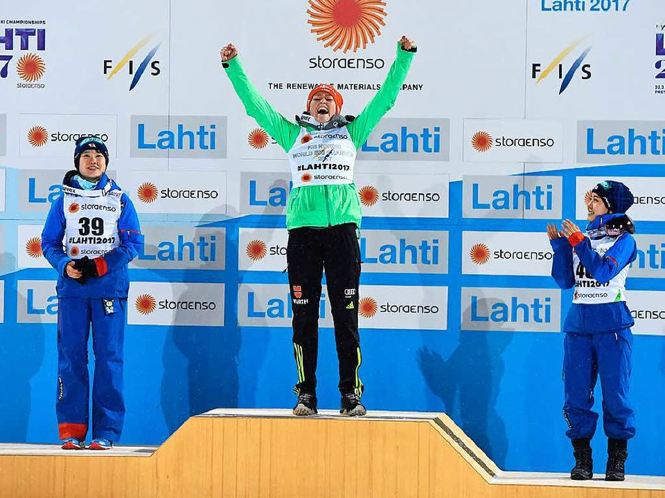 Carina Vogt freut sich auf dem Podium.  | Foto: AFP