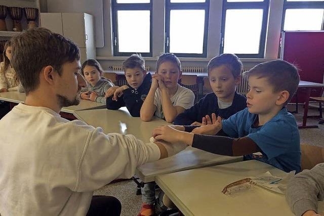 Kinder lernen, wie man Verbände anlegt und Hilfe holt