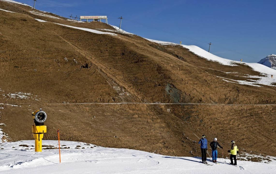 Skifahrer stehen bei einer Schneekanon...d aus Kunstschnee in Arosa (Schweiz).   | Foto: dpa
