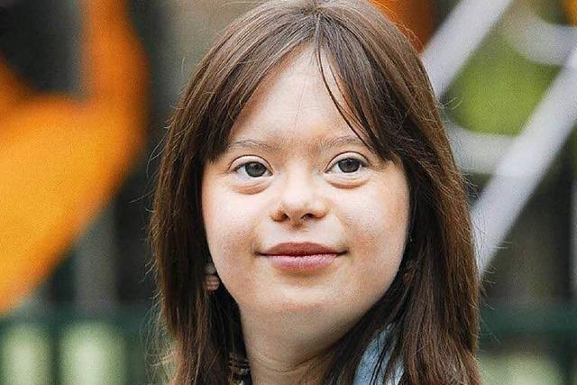 Junge Frau mit Down-Syndrom präsentiert das Wetter