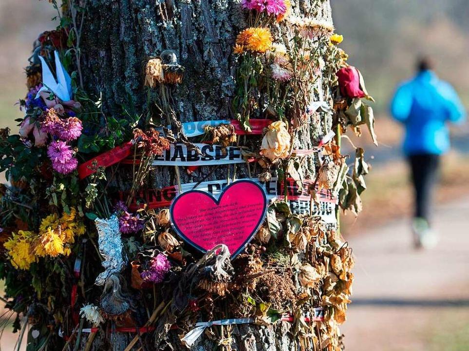 Blumen an einem Baum unweit des Tatorts an der Dreisam im Dezember.  | Foto: dpa