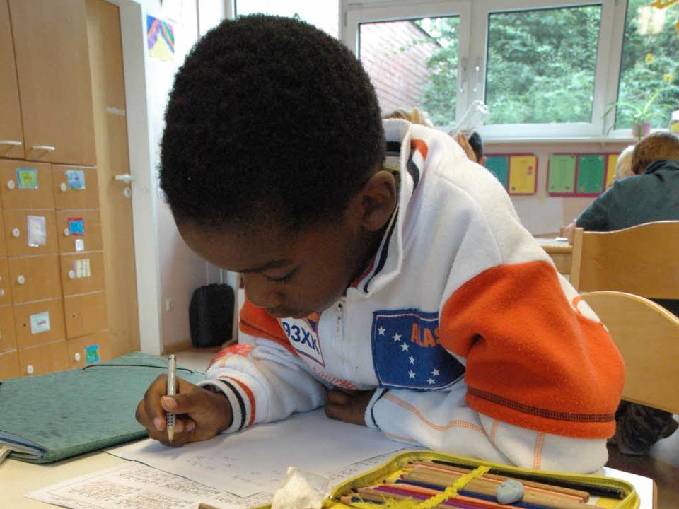 Ein Junge schreibt in einer Betreuungs...eumattschule in ein Heft (Archivbild).  | Foto: Arne Bensiek
