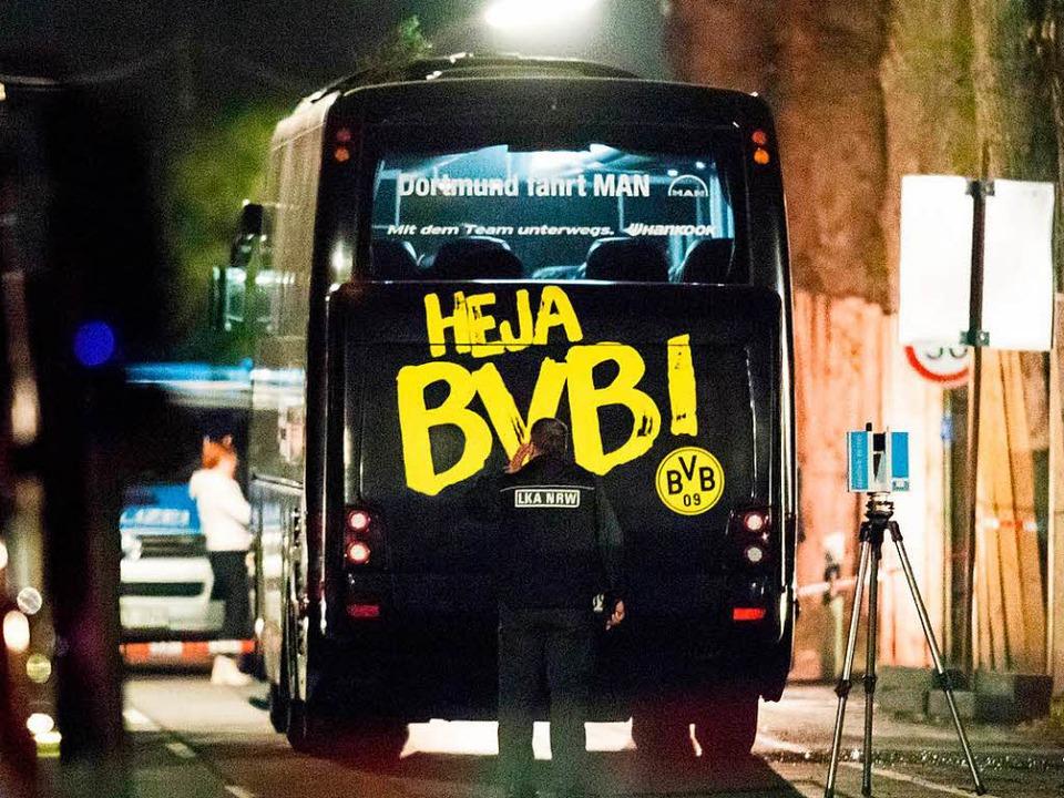 Ein Beamter untersucht den Mannschaftsbus des BVB nach dem Anschlag am Dienstag.  | Foto: dpa