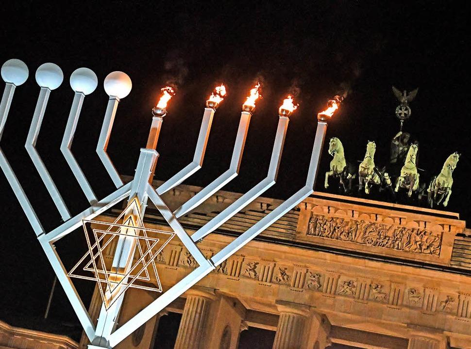 Jüdisches Lichterfest in Berlin: Vor d... wird ein Chanukka-Leuchter entzündet.  | Foto: DPA