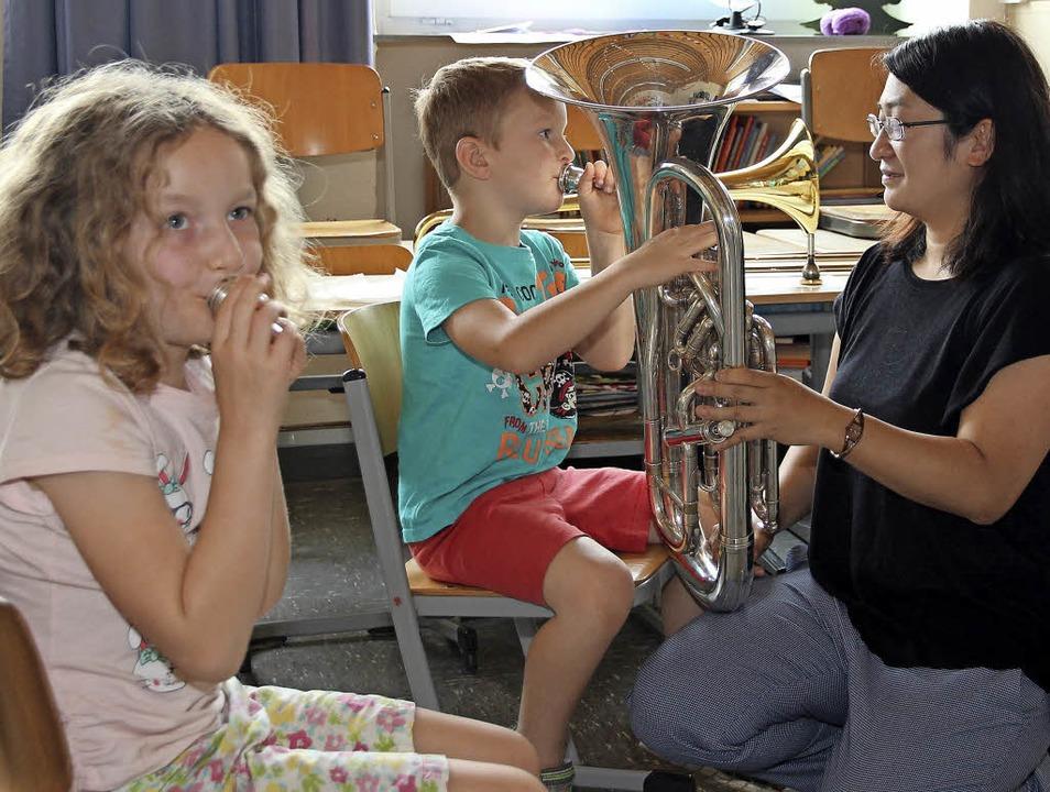 Wer schafft es? Beiden Kinder gelang es Töne dem Instrument zu entlocken.  | Foto: Eva Korinth