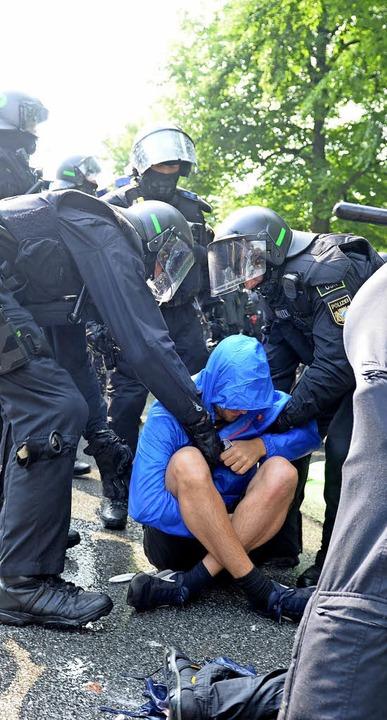 Die Polizei räumt eine Sitzblockade am Freitag.  | Foto: dpa/afp