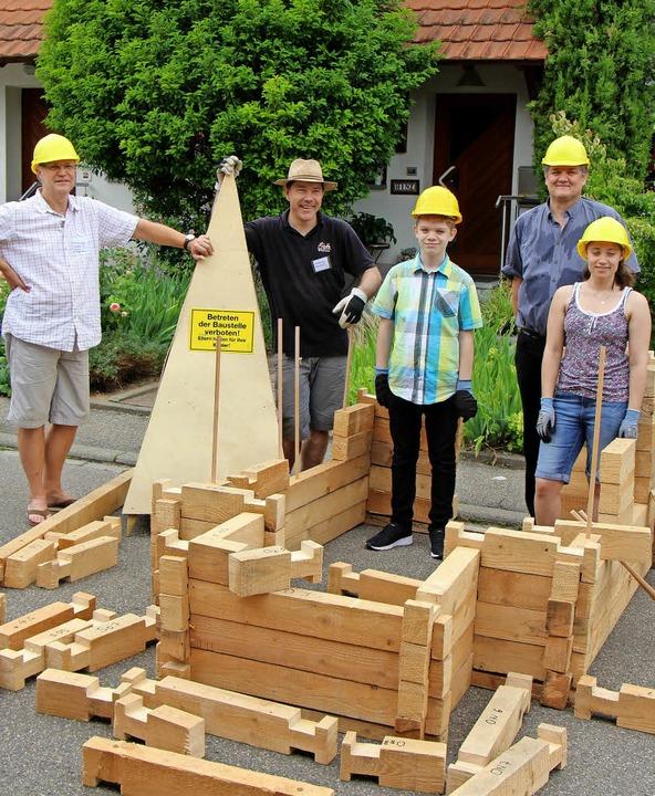 Das Team vom Kirchenbau mit Pfarrer Ch...thel vor den Bauteilen für die Kirche.  | Foto: Helmut Hassler