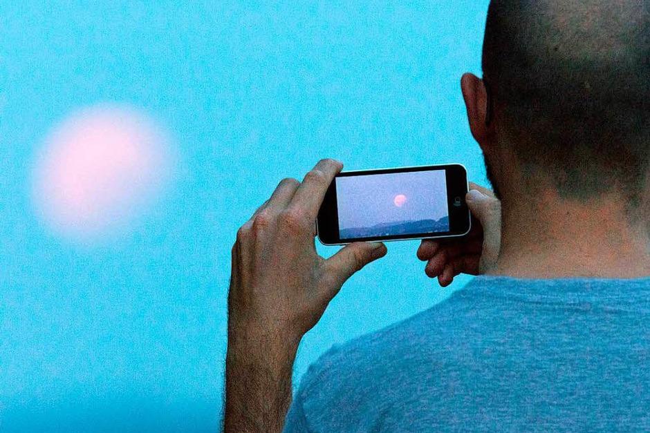 Ein Mann fotografiert  in Bielefeld (Nordrhein-Westfalen) bei einer partiellen Mondfinsternis den Mond mit seinem Handy. (Foto: dpa)