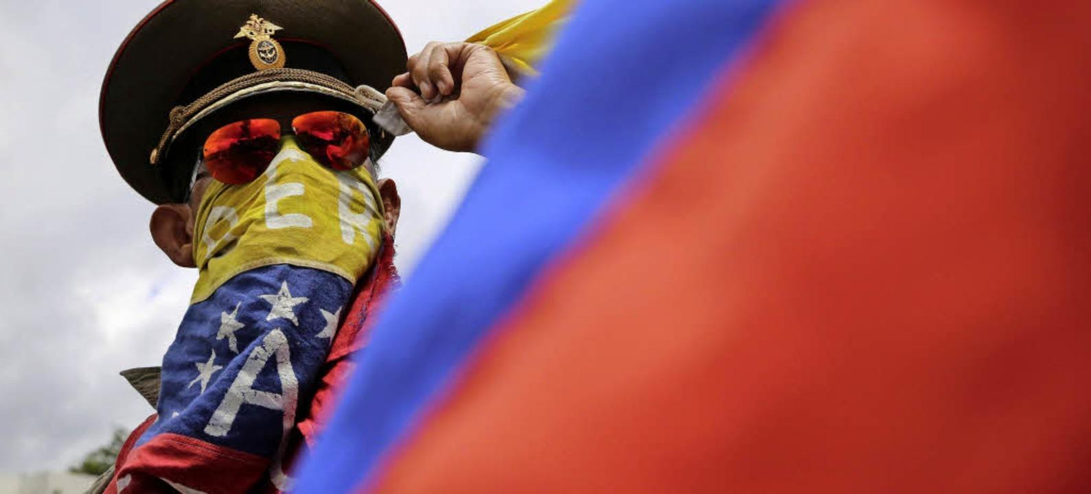 Ein Anti-Regierungs-Demonstrant trägt ... russische Militärmütze auf dem Kopf.     Foto: dpa