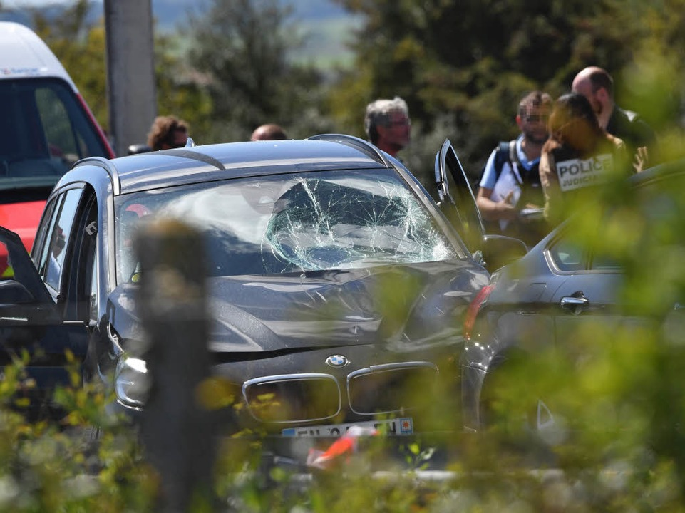 Ermittler stehen bei dem Auto des Verdächtigen  | Foto: AFP
