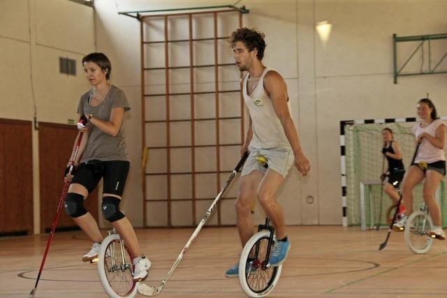 Mit dem Hockeyschläger auf einem Rad