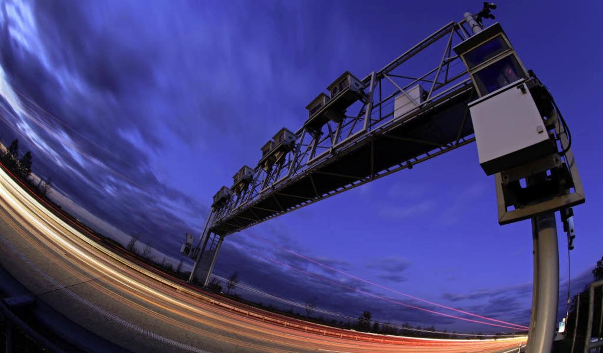 Autos und Lastwagen fahren unter einer...fgenommen mit langer Belichtungszeit.     Foto: dpa