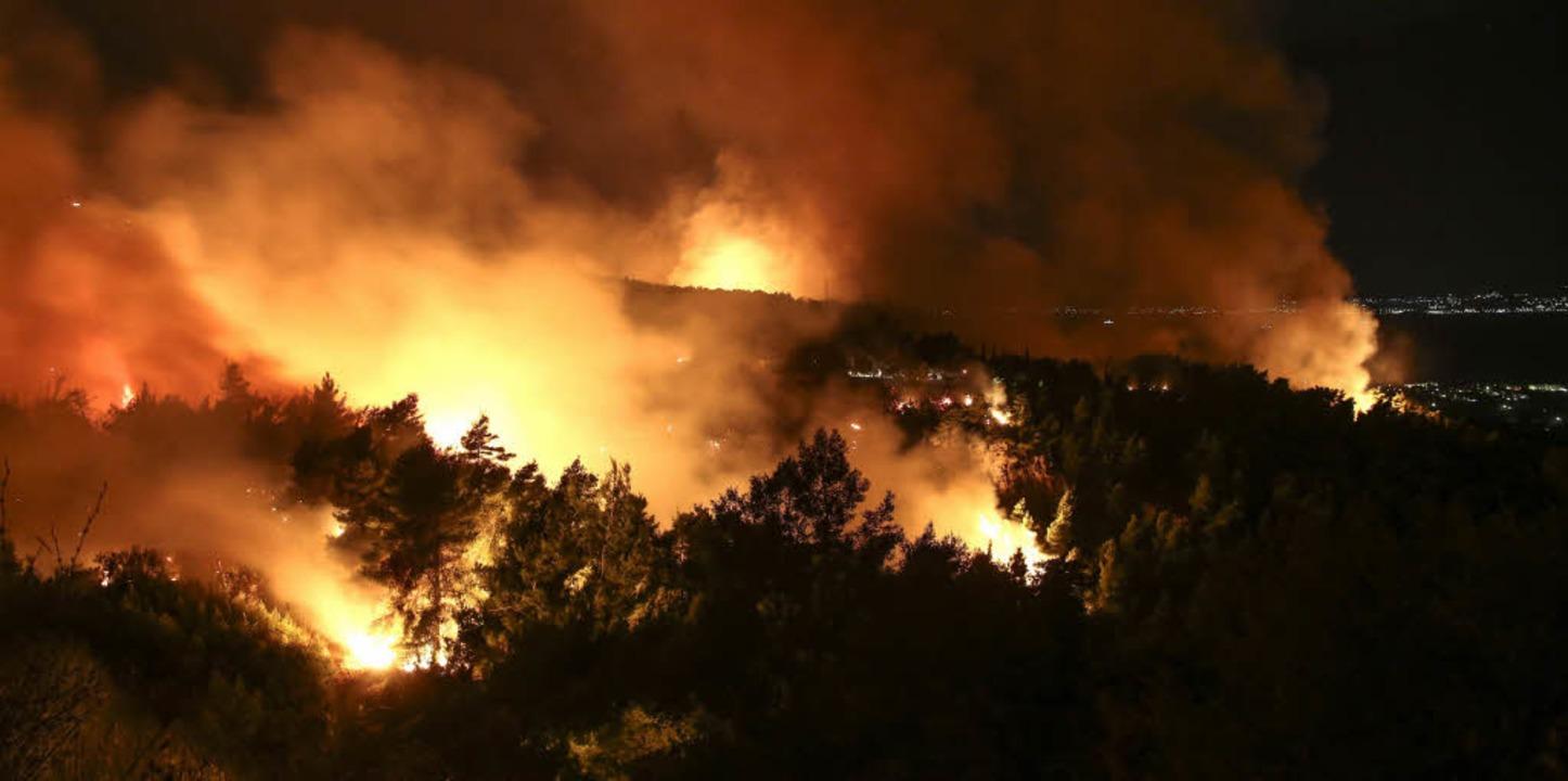 Flammen und Rauch steigen bei einem Waldbrand nahe Kalamos in Griechenland auf.     Foto: dpa