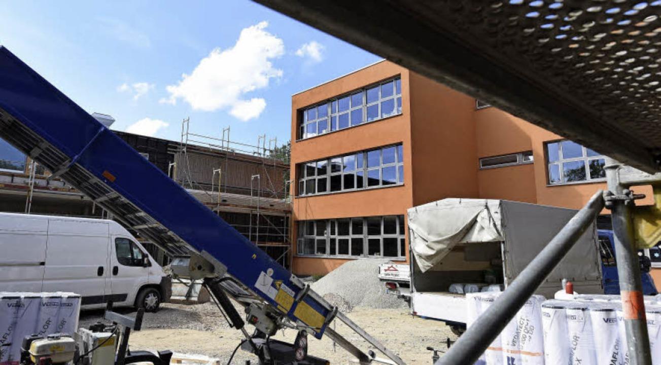 Das alte orangefarbene Schulhaus wird noch saniert.  | Foto: Rita Eggstein
