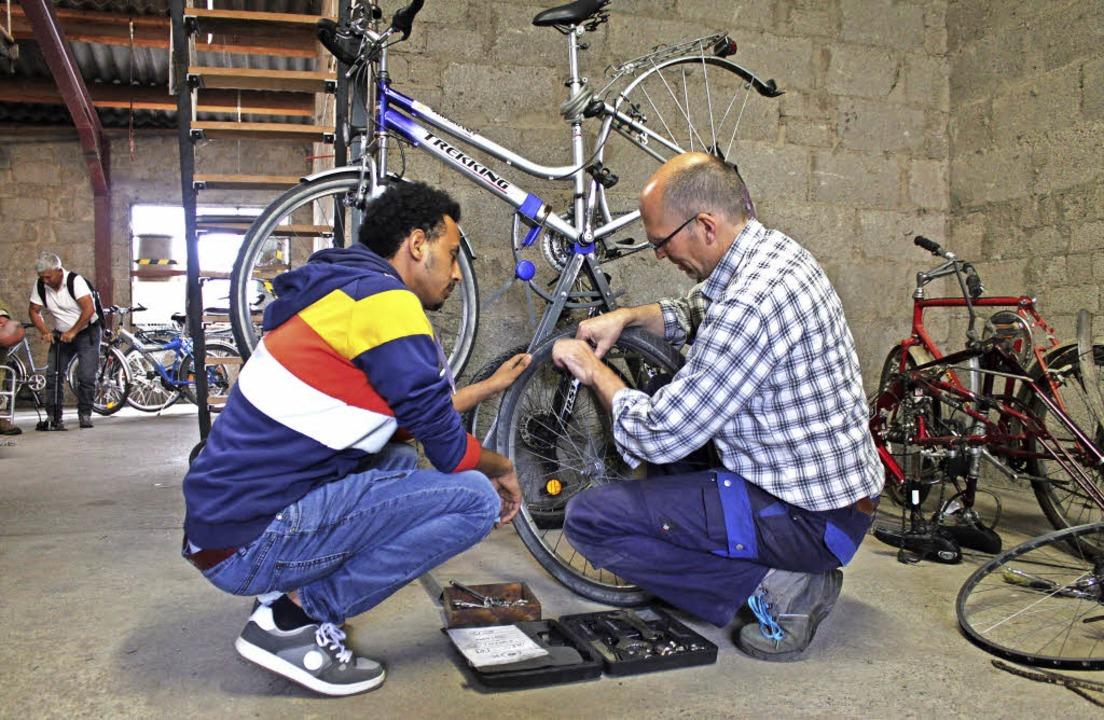 Luiko Czub vom Werkstattteam zeigt ein...ling, wie man einen Reifen repariert.   | Foto: Lara Walter