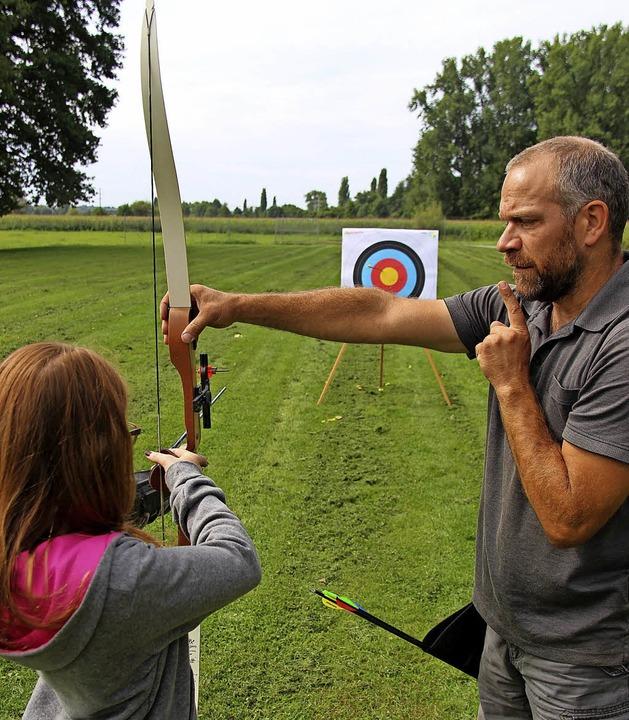 Andreas Kiefer erklärt einem Mädchen, wie es einen Pfeil abschießen muss.   | Foto: Horst David
