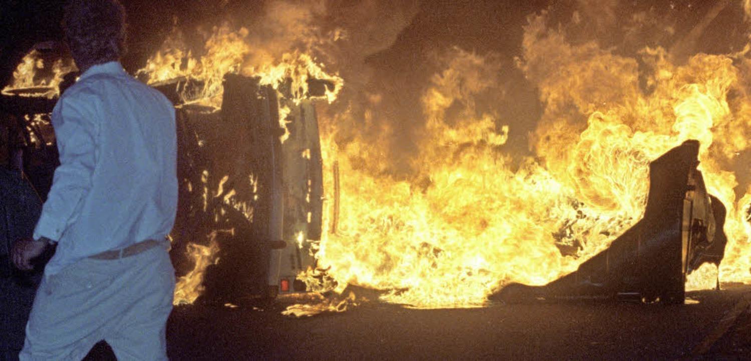 Ein Auto brennt 1992 vor dem Asylbewerberheim in Rostock     Foto: DPA