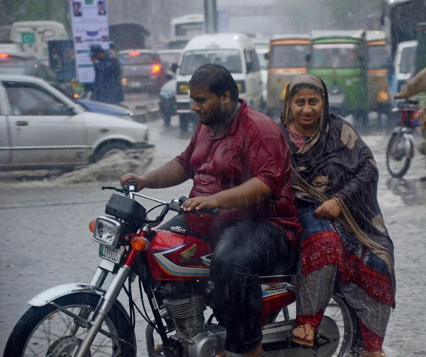 Ein Paar fährt über eine überflutete Straße in Lahore, Pakistan.   | Foto: dpa