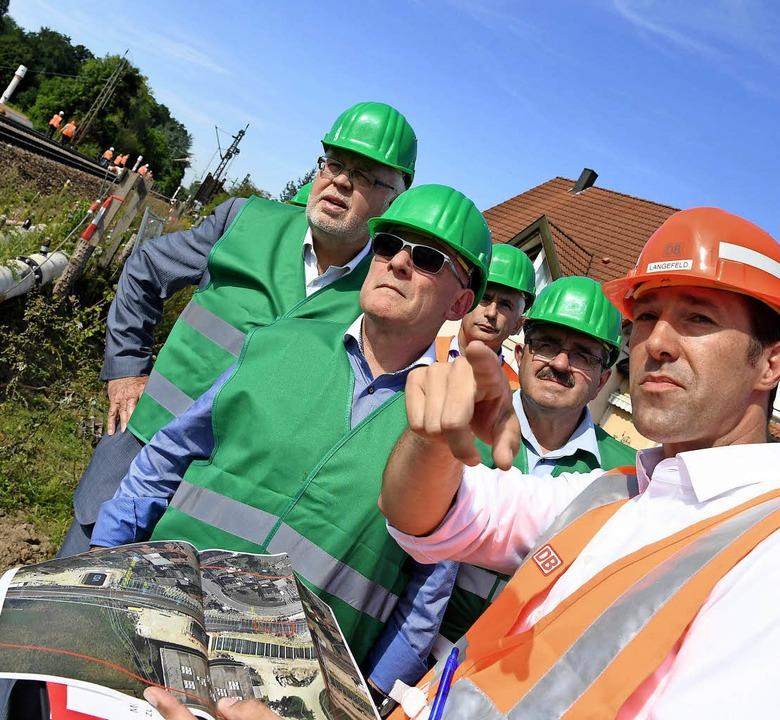 Winfried Hermann lässt sich von Projek...r Bahn-Baustelle in Rastatt erklären.   | Foto: dpa