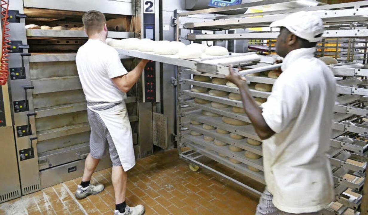 Mit vereinten Kräften schieben die Bäcker die Laibe in den heißen Ofen.     Foto: Silas Schwab