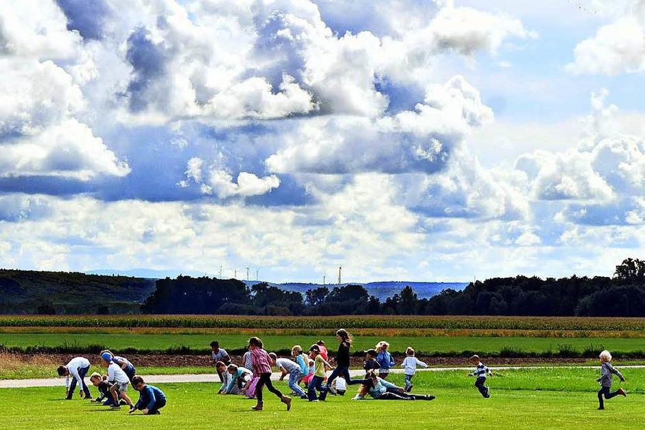 Süßer Spaß: Ein Modellflieger hat Bonbons vom Himmel regnen lassen, die Kinder stürzen sich vergnüglich drauf. (Foto: Wolfgang Künstle)