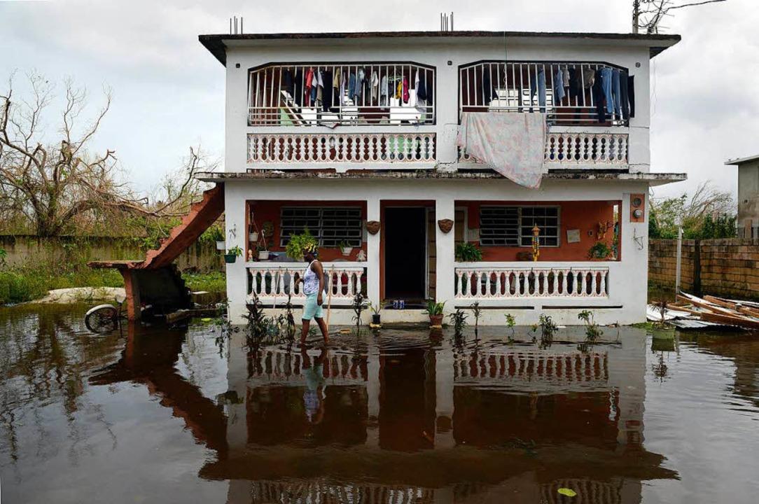 Eine Frau steht vor ihrem Haus umgeben von Hochwasser in Loiza (Puerto Rico)    Foto: dpa