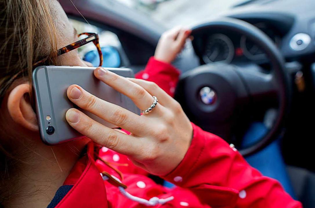 Handy am Steuer: Diese Frau verstößt gegen Verkehrsregeln.    | Foto: dpa