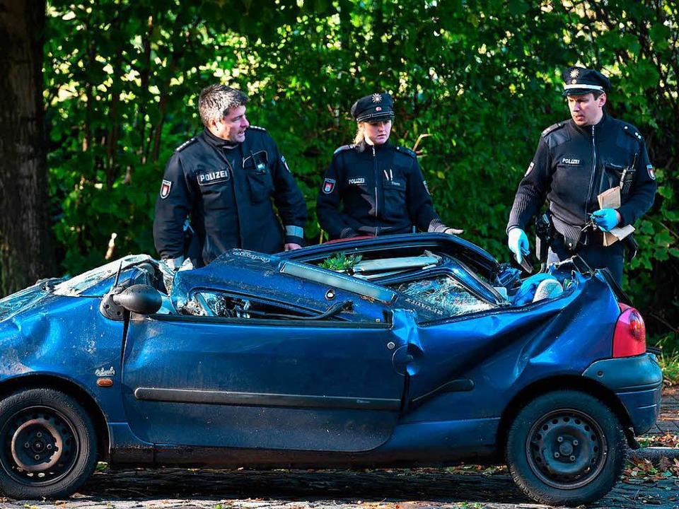 Polizeibeamte stehen in Hamburg Horn vor dem Unfallwagen.  | Foto: dpa