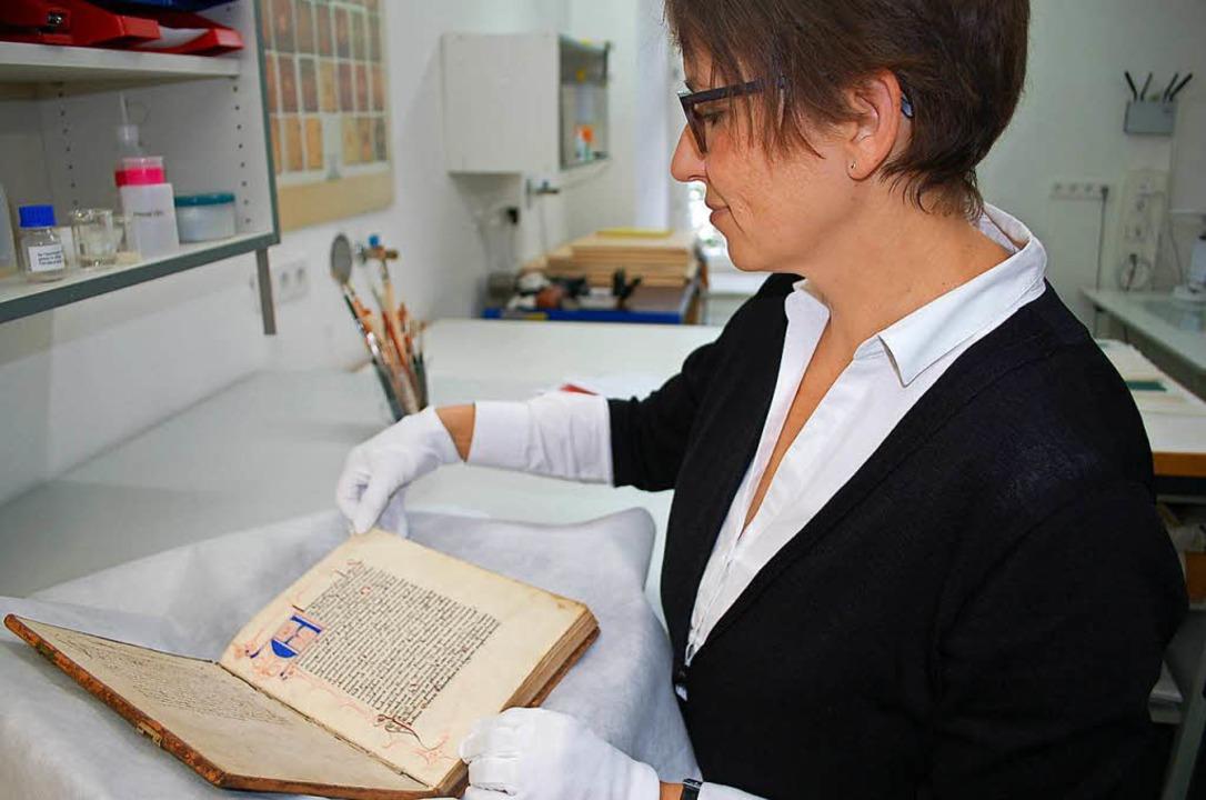 Buchrestauratorin Kerstin Forstmeyer b...dschrift aus dem Freiburger Uniarchiv.  | Foto: Wulf Rüskamp