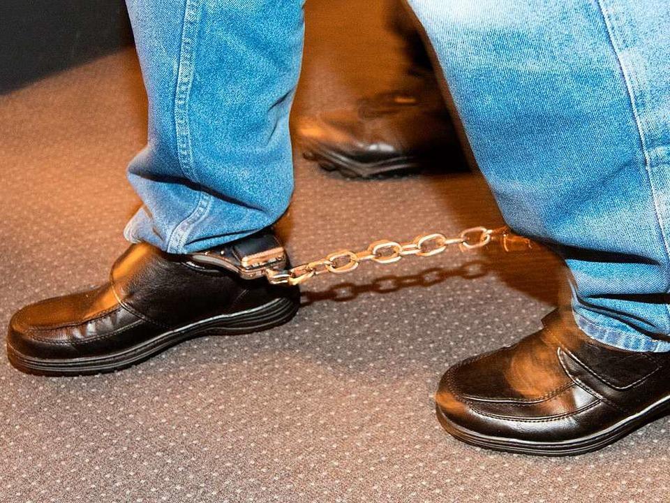 Mit Fußfesseln wird Hussein K. in Saal IV des Landgerichts Freiburg geführt.  | Foto: dpa