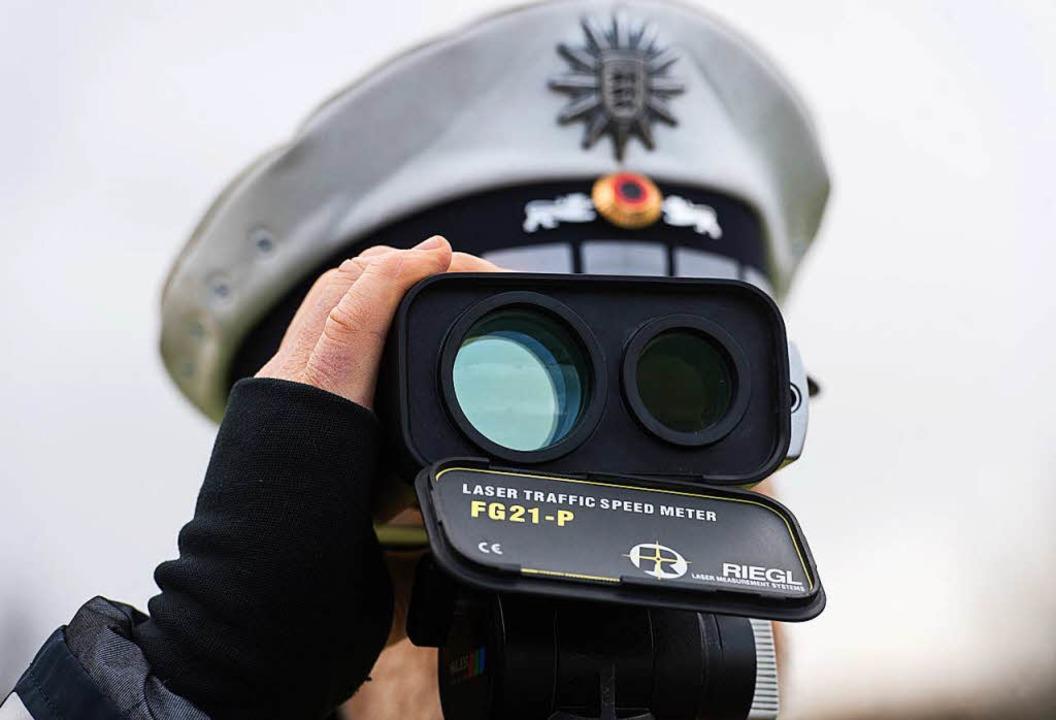 Ein Polizist kontrolliert im Dezember ...mmt es häufig zu illegalen Autorennen.  | Foto: dpa