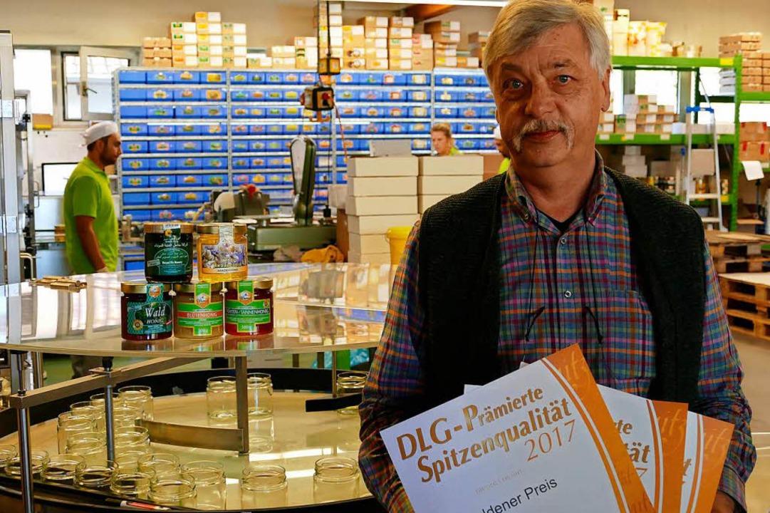 Jürgen Wernet mit den DLG-Urkunden und dem prämierten Honig in der Abfüllhalle.  | Foto: Sophia Kürbs