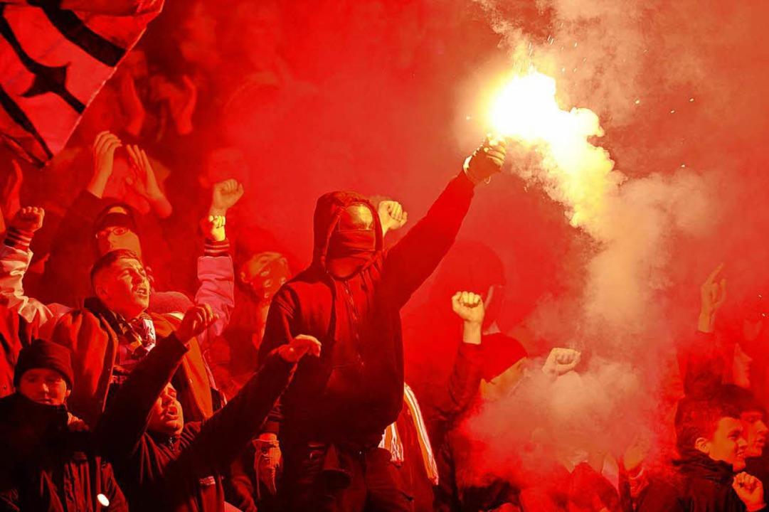 … doch manche Zuschauer – ...11; zünden immer wieder Bengalos an...  | Foto: dpa