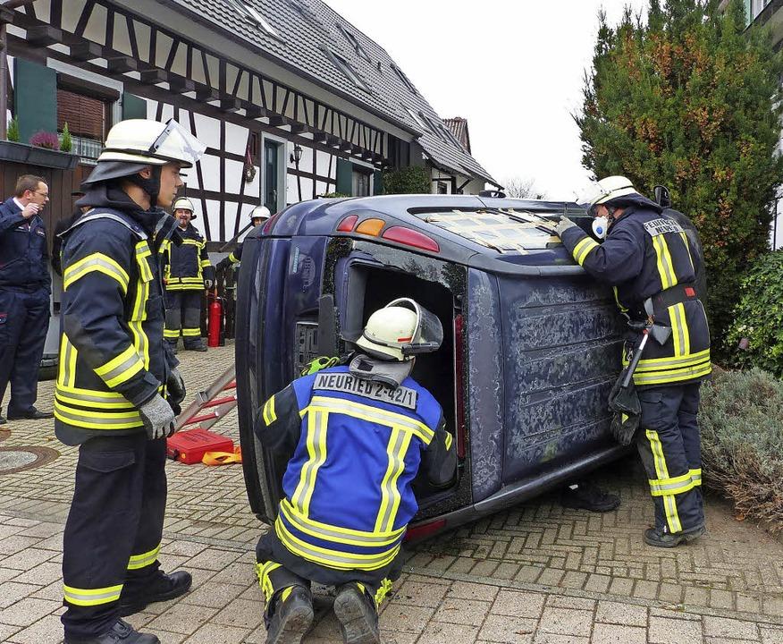 Die Feuerwehr übt die Rettung aus einem umgekippten Auto.   | Foto: D. Fink