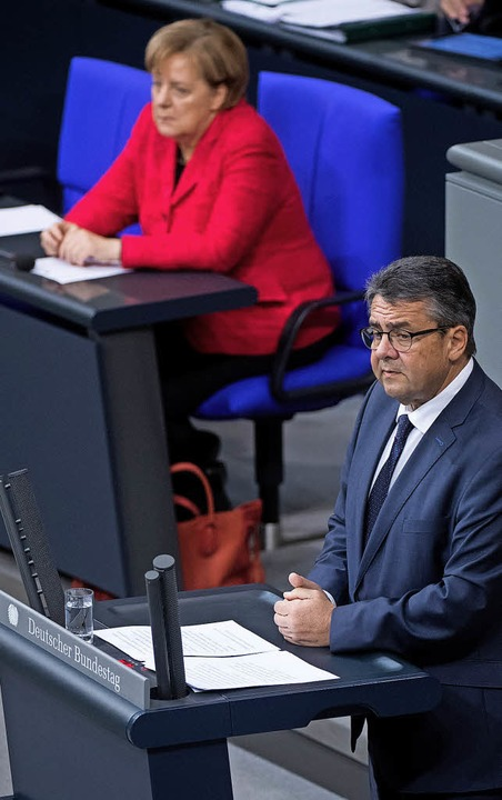 Außenminister Sigmar Gabriel spricht a...m Hintergrund Kanzlerin Angela Merkel.  | Foto: dpa