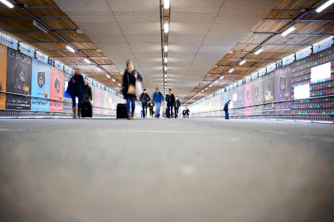 Menschen gehen in Stuttgart durch den ...über die Stuttgart 21 Baustelle führt.  | Foto: dpa