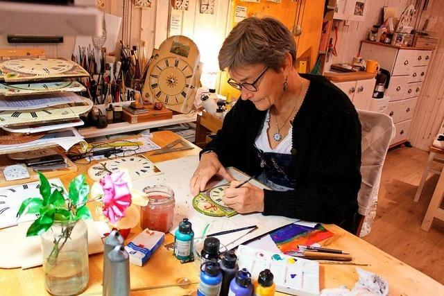 Hinter ihrer Werkstatttür malt Anne-Claire Fink Uhrenschilder