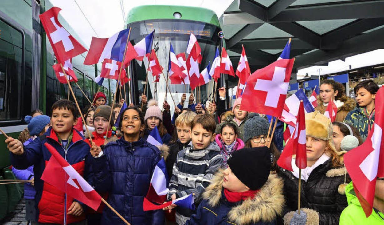 Ein Schulklasse begrüßt die  erste neu...nde Tram nach Frankreich mit Fähnchen.  | Foto: Annette Mahro