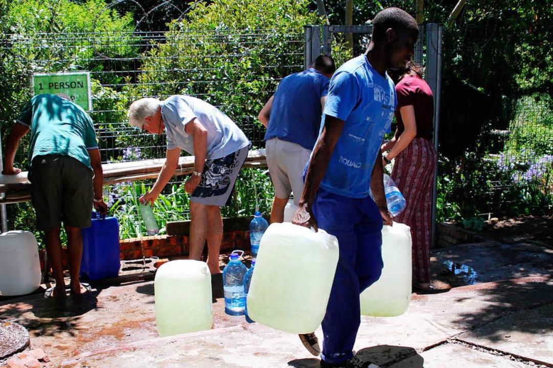 Kapstädter füllen Kanister an einer Quelle mit Wasser auf.   | Foto: DPA