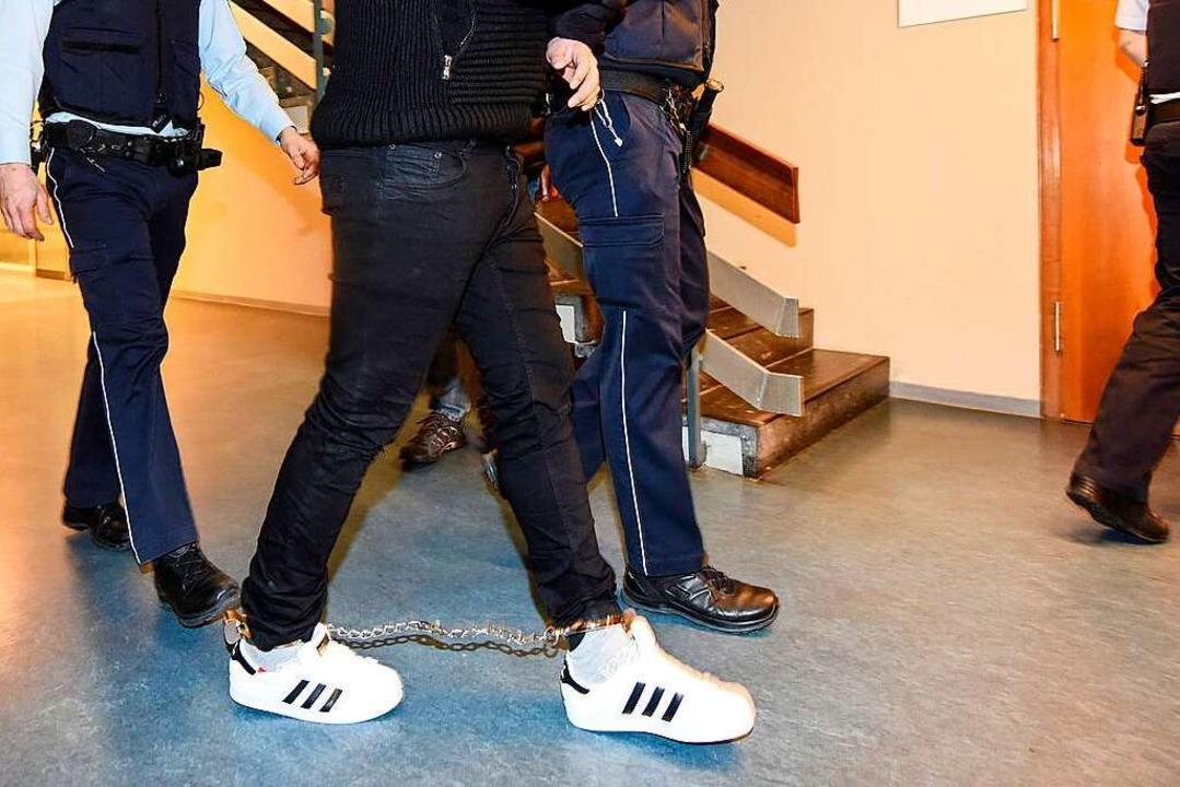 K. wird am Montag von Justizbeamten in den Gerichtssaal gebracht.  | Foto: dpa