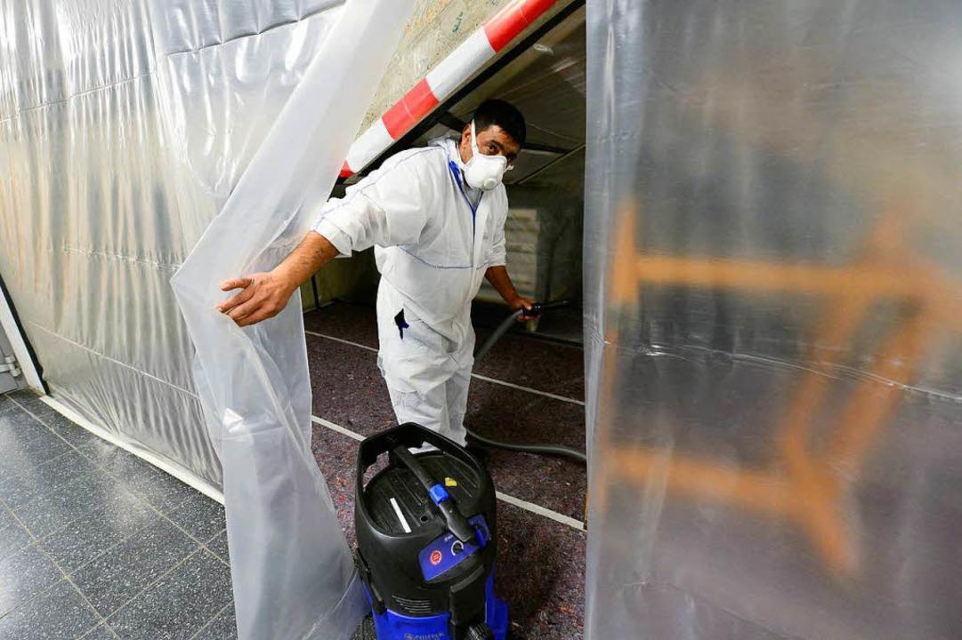 Ein Fachmann im Schutzanzug reinigt hi...ane im  Treppenhaus ein Tischgestell.     Foto: Ingo Schneider