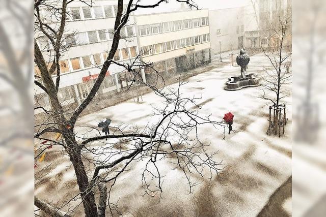 Schneegestöber mit rotem Schirm