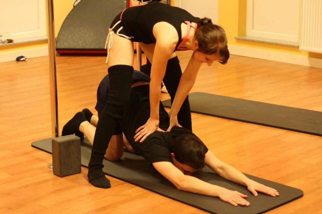 Rücken gerade lassen: Poledance-Traine...ler beim Dehnen vor der Probestunde.bz  | Foto: bz