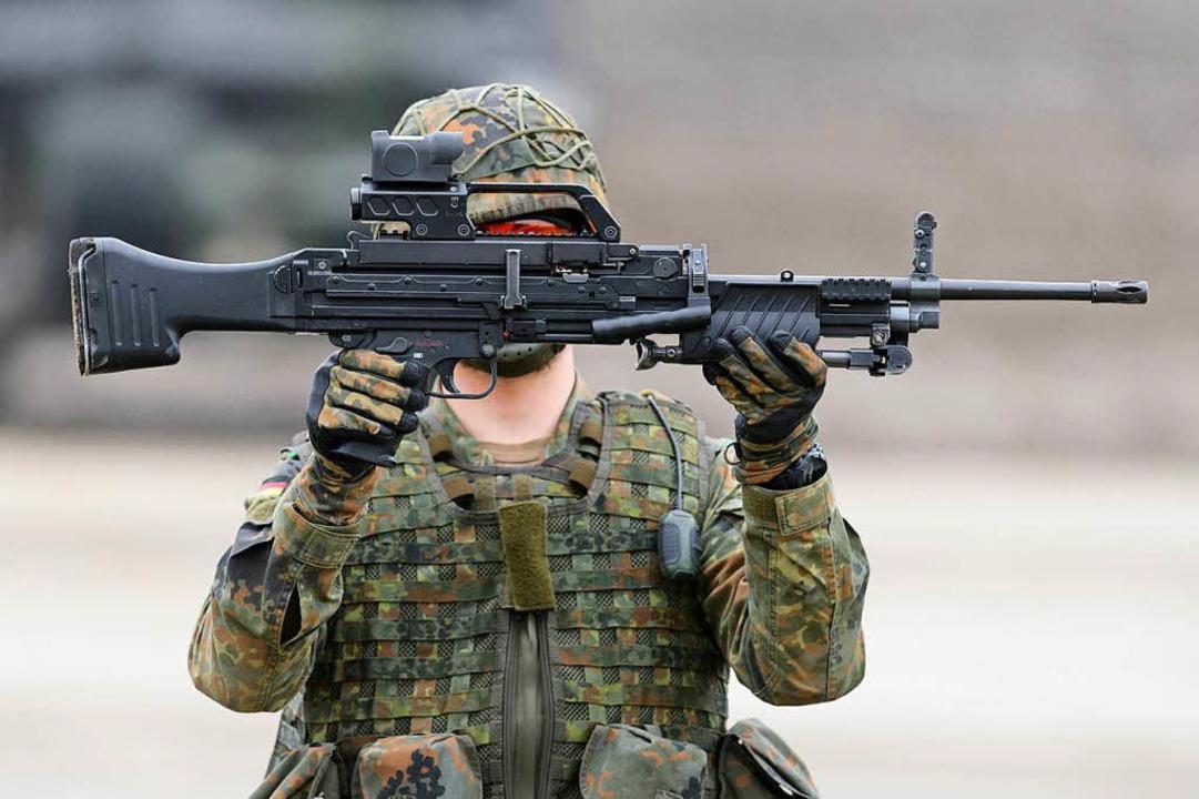 Ein Soldat hält auf einem Truppenübung...Firma Heckler & Koch in der Hand.   | Foto: dpa