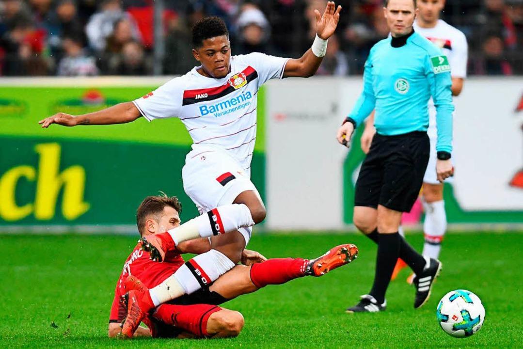 SC-Spieler Amir Abrashi (am Boden) grätscht gegen den Leverkusener Leon Bailey.    Foto: dpa