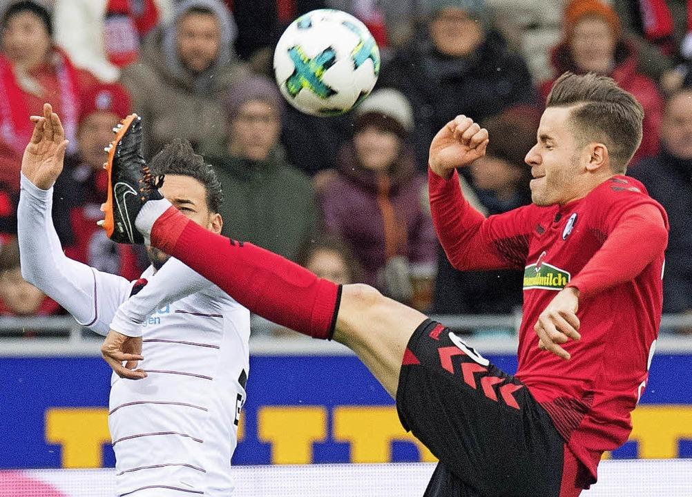Szene eines Kampfspiels: Christian Günter (rechts) gegen Karim Bellarabi  | Foto: dpa