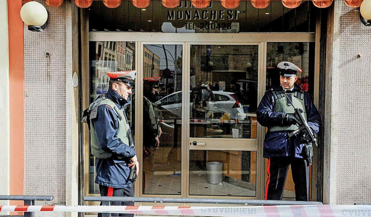 Polizisten überwachen nach der Schießerei in Macerata den Tatort.   | Foto: AFP