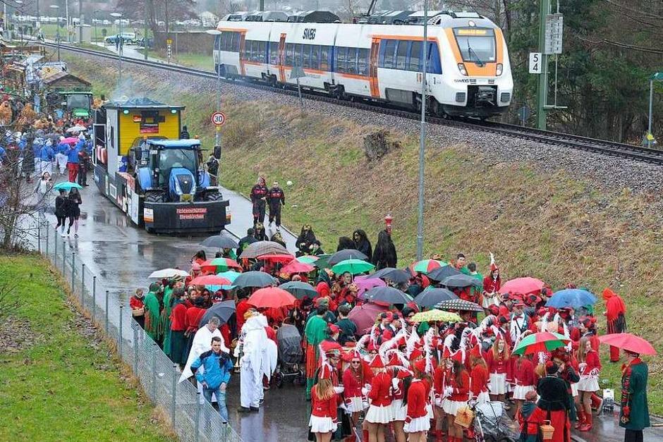 Das Bild des Tages vom Fasnachtszug in Münstertal: Regenschirme auf dem neuen Zugweg entlang der Müsntertalbahn (Foto: Bernhard Seitz)