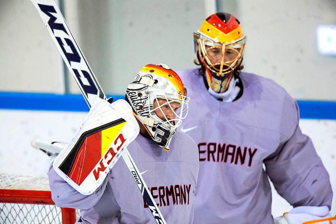 Danny Aus den Birken (links) und Timo ...eongchang mit Jetters Masken aufs Eis.  | Foto: dpa